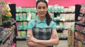 可爱的年轻女推销员画象站立在超级市场的围裙的用她的手横渡了,看照相机和 股票录像