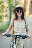 可爱的年轻浅黑肤色的男人室外画象一个帽子的在自行车 免版税库存图片