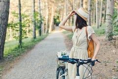 可爱的年轻浅黑肤色的男人室外画象一个帽子的在自行车 免版税图库摄影