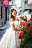 可爱的年轻深色的新娘是微笑和摆在街道在红色花附近 免版税库存图片