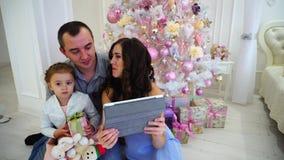 可爱的年轻父母和女婴谈话在有祖母的互联网板材在背景的宽敞卧室光的 股票录像