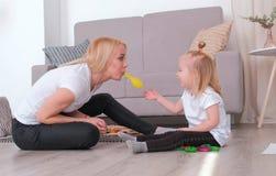 可爱的年轻白肤金发的妈妈膨胀她坐在沙发附近的迷人的女儿的一个气球 家庭消遣 库存图片
