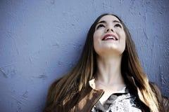 可爱的年轻行家妇女站立反对蓝色木墙壁背景激动在她的面孔的 免版税图库摄影