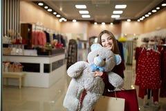 可爱的年轻逗人喜爱的白种人妇女拥抱长毛绒与购物袋的玩具熊在服装店前面 俏丽的女孩 免版税库存照片