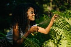 可爱的年轻非洲女孩的旁边室外画象有绿色唇膏的使用绿色塑料触发器浪花 免版税图库摄影