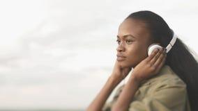 可爱的年轻非洲女孩的旁边画象有自然构成的听到在耳机的音乐在 免版税图库摄影