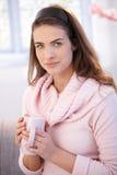 可爱的微笑妇女饮用的茶在家 图库摄影