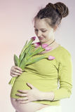 可爱的微笑的孕妇画象有郁金香的 库存图片