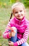 可爱的微笑的小女孩坐草 图库摄影