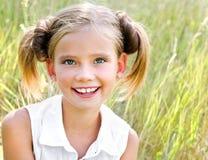 可爱的微笑的小女孩孩子画象室外的礼服的 图库摄影