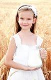 可爱的微笑的小女孩用在麦田的牛奶 免版税库存图片