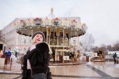 可爱的微笑的模型穿被编织的帽子和皮大衣,摆在ne 免版税库存照片