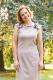 可爱的微笑的白种人种族少妇画象在公园 免版税库存图片