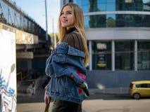 可爱的微笑的白肤金发的女孩在桥梁站立以大厦为背景 免版税库存图片