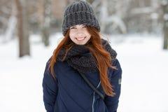 年轻可爱的微笑的红头发人妇女特写镜头美丽的冬天画象在逗人喜爱的被编织的帽子冬天多雪的公园 库存图片