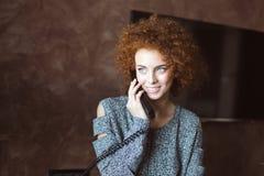 可爱的快乐的少妇在家谈话在电话 库存照片