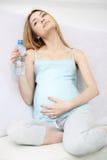 可爱的怀孕的女孩喝水 免版税库存图片