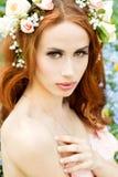 年轻可爱的性感的女孩在一个晴天开花与在红色头发的花 库存图片