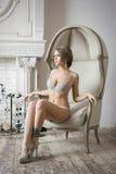 可爱的性感的白肤金发的新娘妇女坐椅子 免版税库存图片