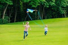 可爱的愉快的使用与在绿色草甸的风筝的兄弟和姐妹 库存图片