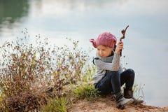 可爱的愉快的儿童女孩使用用在河边的棍子在晴天 免版税库存图片