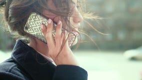 可爱的愉快的女孩谈话在街道上的电话 股票视频