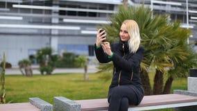 年轻可爱的愉快的妇女在公园射击自己- selfie 股票视频
