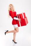 可爱的愉快的妇女在红色圣诞老人服装藏品presen 免版税库存照片