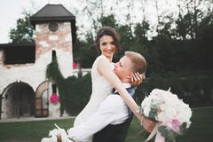可爱的愉快的婚礼夫妇,有摆在美丽的城市的长的白色礼服的新娘 库存图片