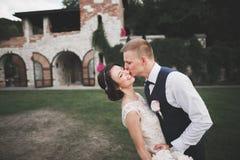 可爱的愉快的婚礼夫妇,有摆在美丽的城市的长的白色礼服的新娘 免版税库存图片
