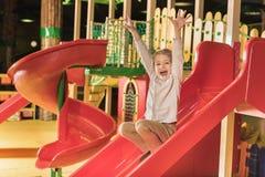 可爱的愉快的小男孩用使用在幻灯片的被举的手 库存图片
