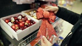 可爱的愉快的少妇选择在商店圣诞节弓 家庭内部的装饰 一棵Xmas树的球在模糊 影视素材