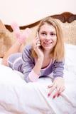 可爱的愉快的微笑的少妇在睡衣的床上谈话在流动手机愉快的微笑的&看的照相机 免版税图库摄影