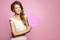 可爱的愉快的微笑的美丽的妇女画象有桃红色心脏的,爱假日在桃红色背景的华伦泰标志 库存照片
