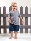 可爱的愉快的男孩常设篱芭 免版税库存照片