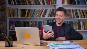可爱的成人愉快的商人有在坐在膝上型计算机前面的片剂的一视频通话在图书馆户内 影视素材