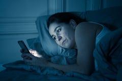 可爱的拉丁妇女后使上瘾对手机和互联网在在附近在看起来的床上失眠 免版税库存图片