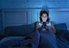 可爱的拉丁妇女后使上瘾对手机和互联网在在附近在看起来的床上失眠 库存照片