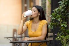 可爱的拉丁妇女坐的饮用的咖啡 免版税库存照片