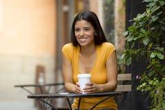 可爱的拉丁妇女坐的饮用的咖啡 图库摄影