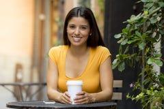 可爱的拉丁妇女坐的饮用的咖啡 免版税库存图片