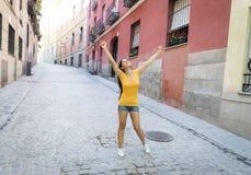 年轻可爱的拉丁妇女愉快和激动摆在现代都市欧洲城市 图库摄影