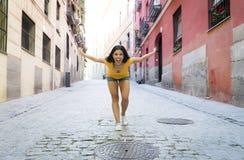 年轻可爱的拉丁妇女愉快和激动摆在现代都市欧洲城市 皇族释放例证