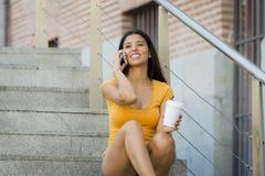 可爱的拉丁妇女愉快她的二十谈她的流动巧妙的电话 库存照片
