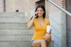 可爱的拉丁妇女愉快她的二十谈她的流动巧妙的电话 库存图片
