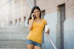 可爱的拉丁妇女愉快她的二十谈她的流动巧妙的电话 免版税库存照片