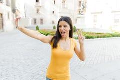 可爱的拉丁妇女谈话在她巧妙的电话 库存图片