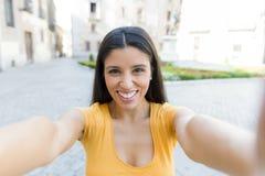 可爱的拉丁妇女谈话在她巧妙的电话 库存照片