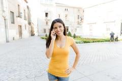 可爱的拉丁妇女谈话在她巧妙的电话 免版税库存照片