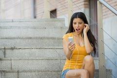 可爱的拉丁妇女shokced看她的电话 免版税库存图片